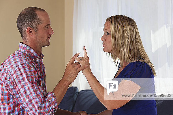 Husband and wife with hearing impairments signing 'I love you' in American sign language
