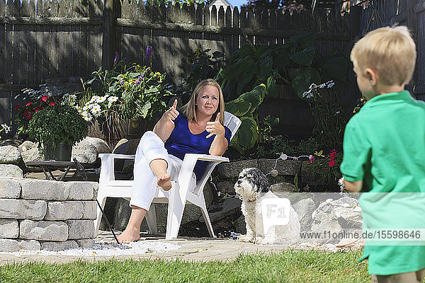Mother and son with hearing impairments playing football and signing 'play' in American sign language in backyard