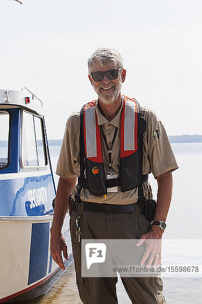 Portrait of a public works engineer standing near a service boat and smiling