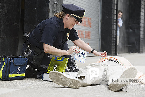 Woman police officer administering defibrillator to a senior man