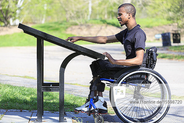 Man who had Spinal Meningitis in a wheelchair reading a park directory