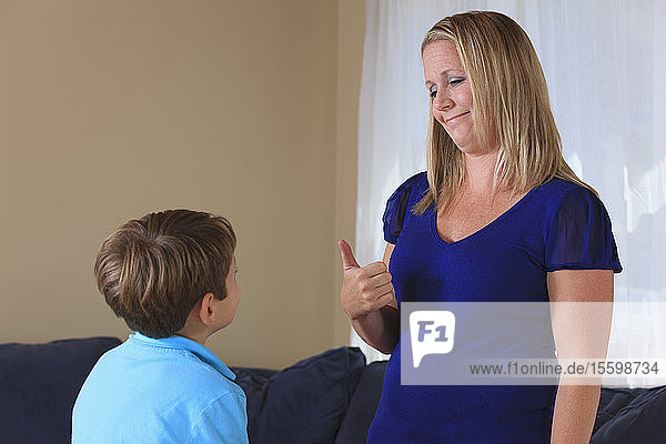 Mother and son with hearing impairments signing 'good job' in American sign language