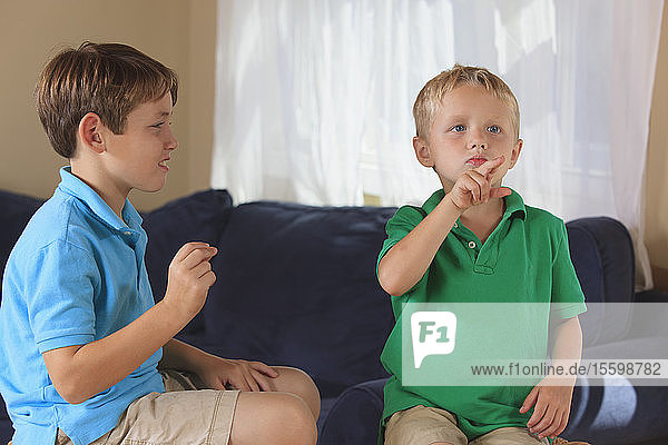Boys with hearing impairments signing 'duck' in American sign language on their couch