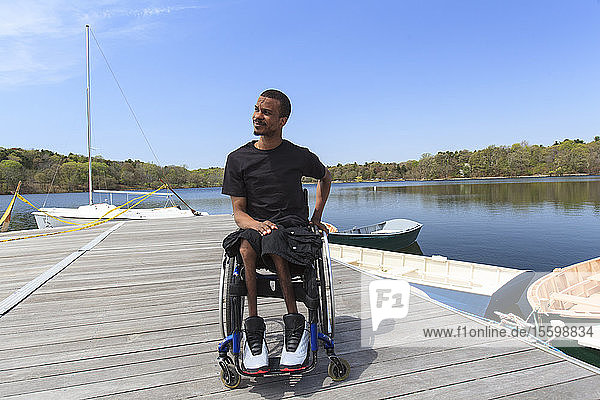 Man who had Spinal Meningitis in a wheelchair sitting on a dock
