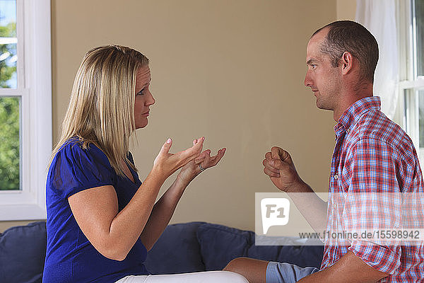 Husband and wife with hearing impairments signing 'Want  Yes' in American sign language