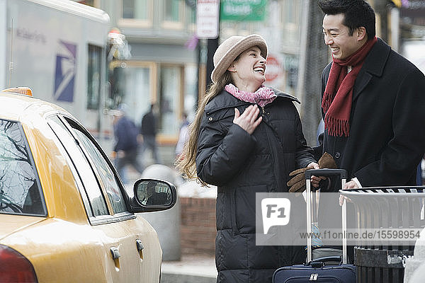 Young couple looking at each other and smiling near a taxi