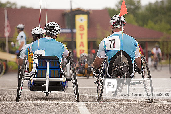 Men with spinal cord injury and leg amputee participating in a handcycle race