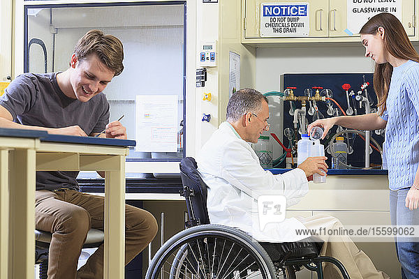 Professor with a spinal cord injury in a wheelchair working with students in an engineering lab filling container with distilled water