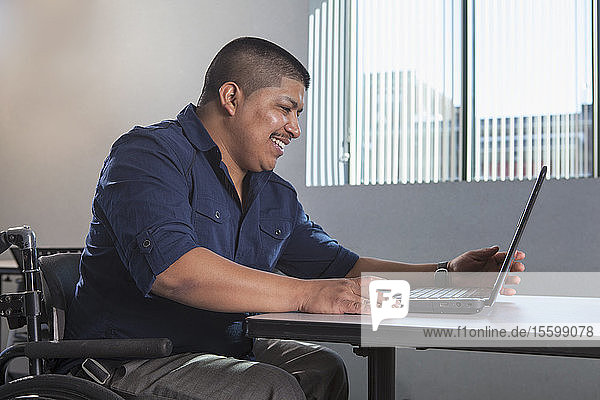 Hispanic man with Spinal Cord Injury working in an office