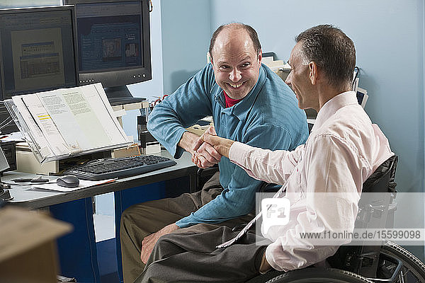 Two businessmen shaking hands in an office  one with Friedreich's Ataxia and another with spinal cord injury