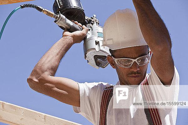 Carpenter using a nail gun