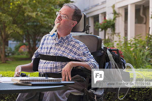 Businessman with Duchenne muscular dystrophy using breathing ventilator and doing paperwork at a cafe