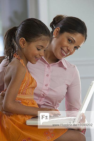 Hispanic woman assisting her daughter in using laptop