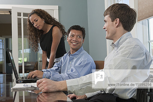 Businessman with spinal cord injury with his colleagues in an office