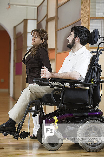 Side view of a man with Cerebral Palsy and woman.