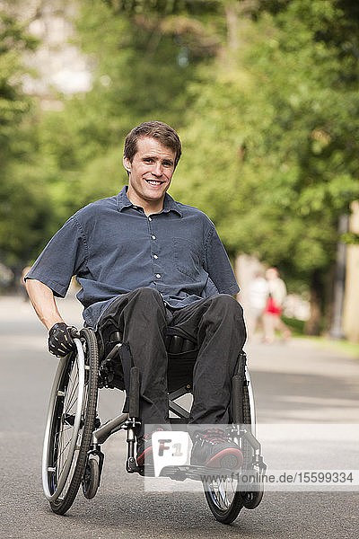 Man with spinal cord injury in a wheelchair maneuvering wheelchair on path through public park