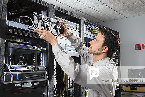Network engineer putting rack mounted coaxial switches in place
