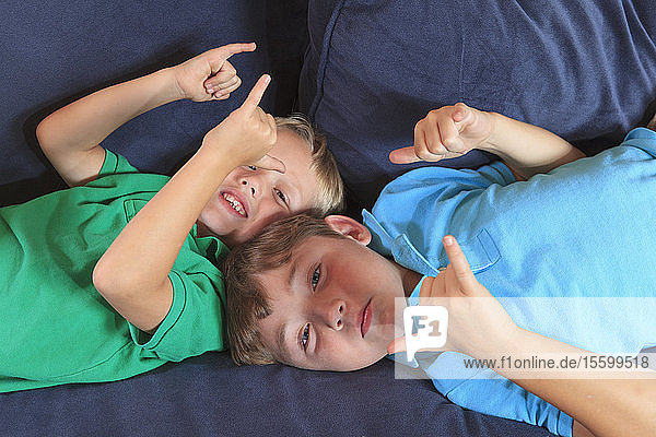 Boys with hearing impairments signing 'play' in American sign language on their couch