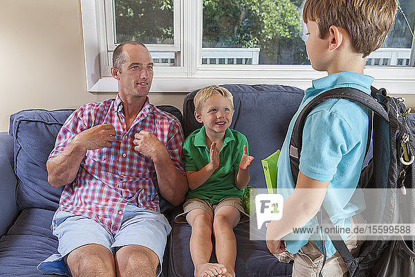 Father and sons with hearing impairments signing 'school  backpack' in American sign language on their couch
