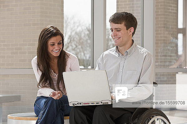Teacher with spinal cord injury and a student using a laptop