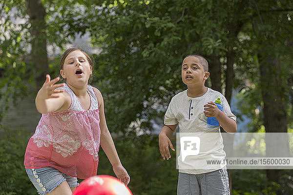 Hispanic boy with Autism playing outside with his sister