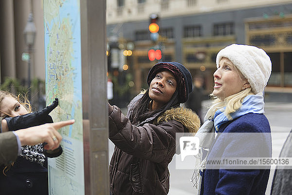 Tourists looking at a street map in Government Center  Boston  Suffolk County  Massachusetts  USA
