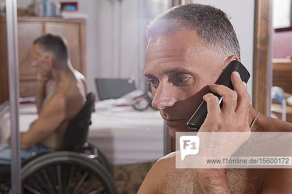 Man with spinal cord injury talking on a mobile phone