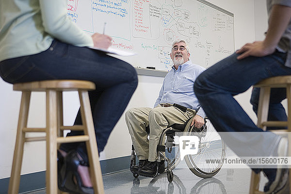 University professor with Muscular Dystrophy teaching his students in a classroom