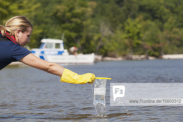 Public works engineer taking public water samples from reservoir