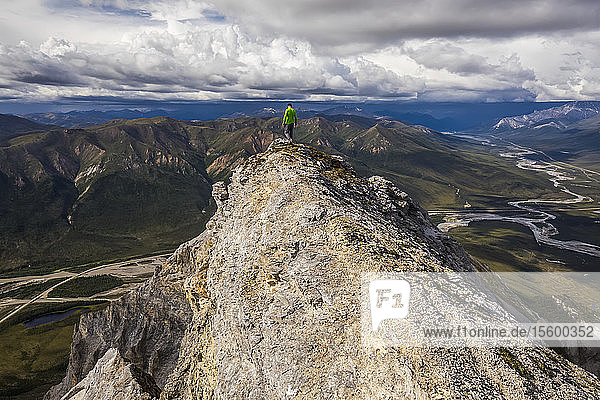 A hiker treads carefully above cliffs near the summit of Sukakpak Mountain in the Brooks Range; Alaska  United States of America
