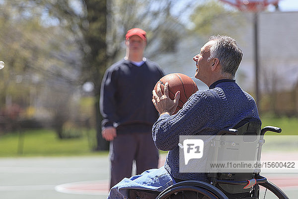 Father with Spinal Cord Injury and his son with Down Syndrome playing basketball in a park