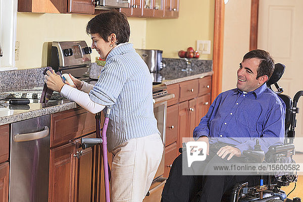 Woman with Cerebral Palsy using crutches and working in her kitchen while talking to her husband with Cerebral Palsy