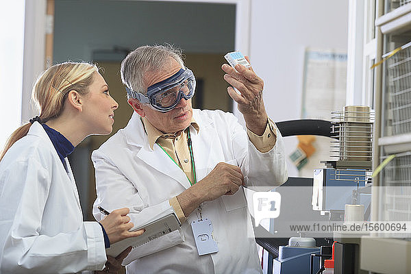 Professor working with engineering student looking at reference samples for thermogravimetric analyzer in a laboratory