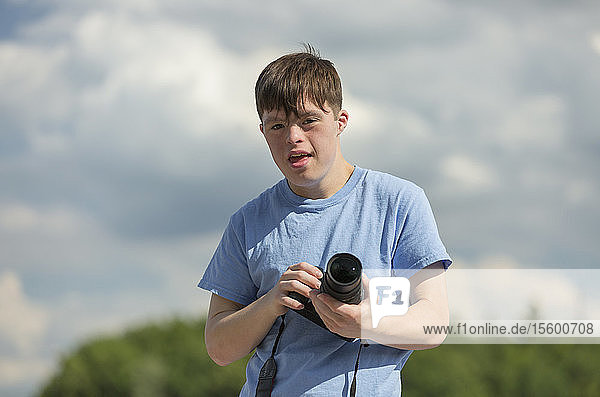 Young man with Down Syndrome holding a camera