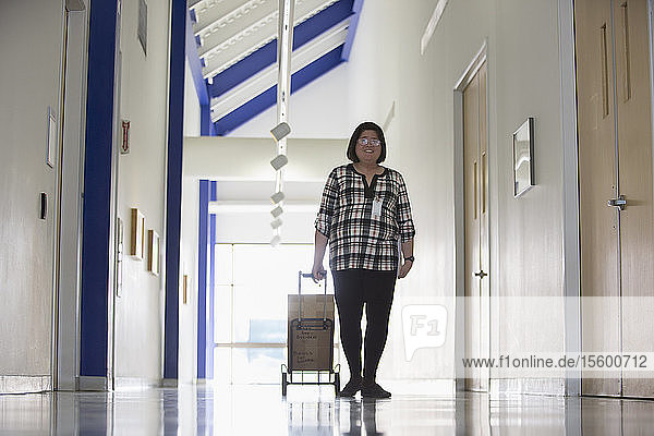 Asian woman with a Learning Disability taking boxes down an office hallway