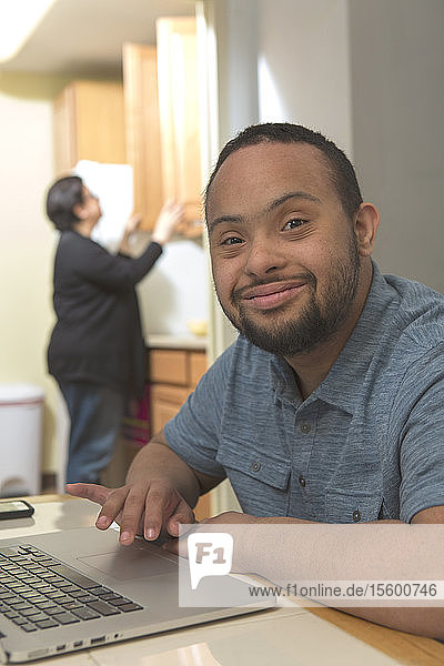 Happy African American man with Down Syndrome using a laptop at home with his mother in background
