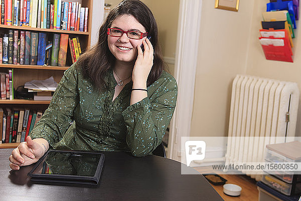 Woman with Asperger syndrome working with her smart phone and tablet from home office
