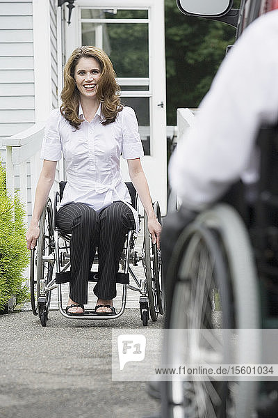Mid adult woman sitting in a wheelchair with a Spinal Cord Injury and smiling