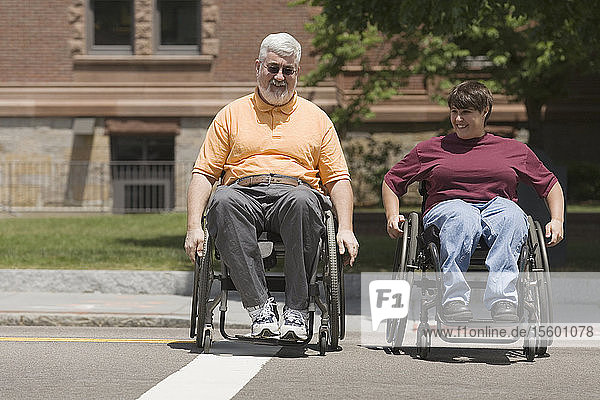 Man and woman with Muscular Dystrophy crossing a road in wheelchairs