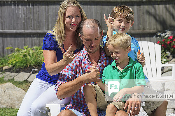 Portrait of a happy family with hearing impairments signing 'I love you' in American sign language