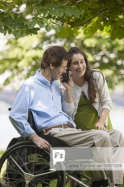 Pregnant wife listening to smart phone with husband in wheelchair with spinal cord injury