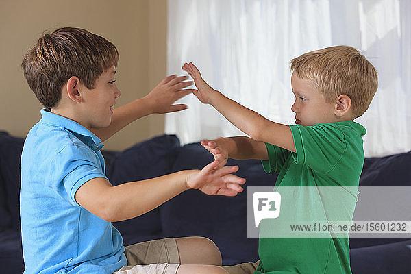 Boys with hearing impairments signing 'safe' in American sign language on their couch