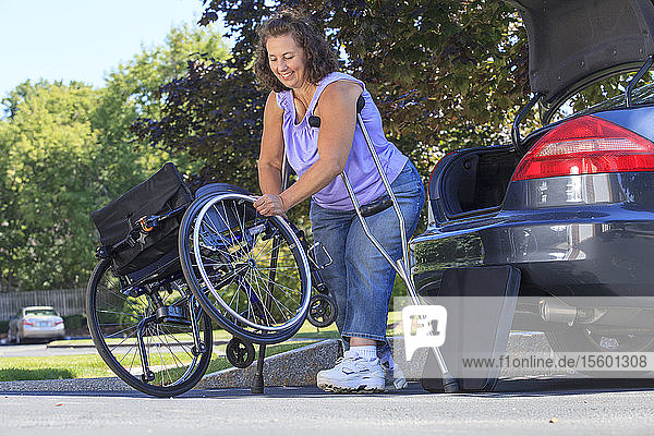 Woman with Spina Bifida using crutches to put wheelchair together after traveling in the car