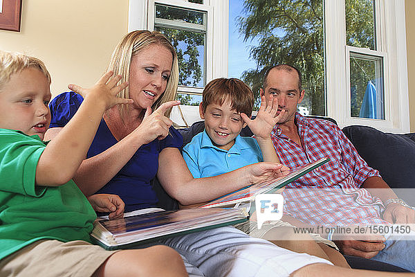 Family with hearing impairments watching photo album and signing 'who  Daddy' in American sign language on their couch