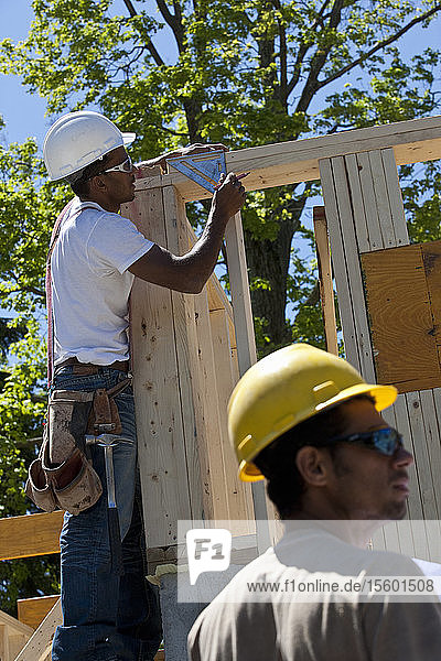 Carpenters measuring angle of frame