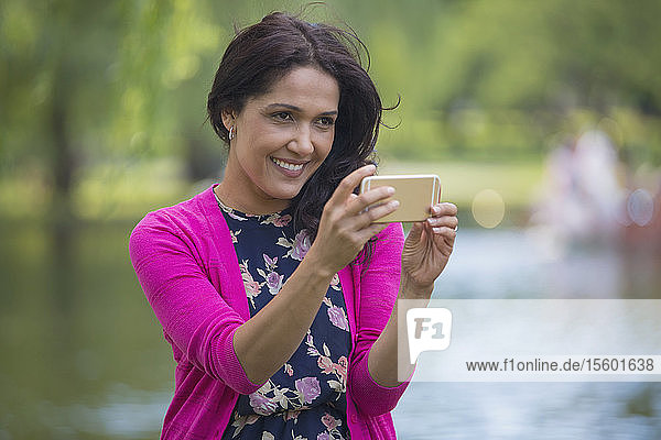Happy Hispanic woman using her mobile phone in a park