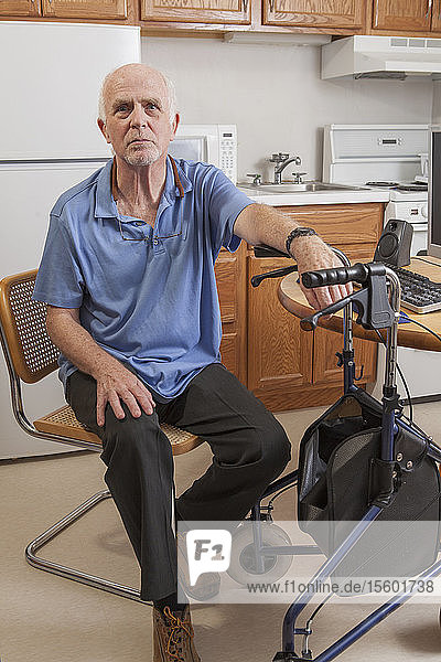 Man with Ataxia holding his walker and sitting at the computer