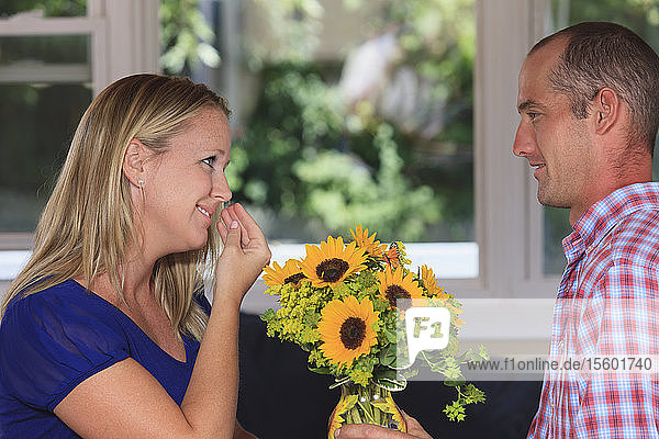 Husband giving flowers to his wife signing 'Flower' in American sign language both with hearing impairments