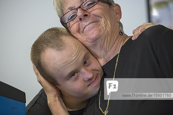 Waiter with Down Syndrome hugging another colleague