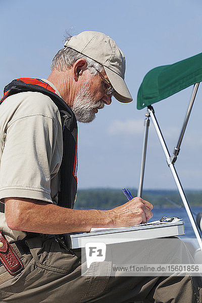 Public works engineer on service boat recording data on public water samples from reservoir